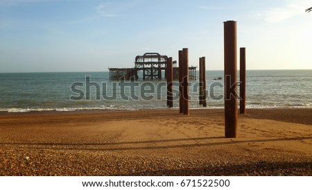 a view to the old Brighton pier. the cast iron legs sit proud from the golden sand at this british sea side. #671522500