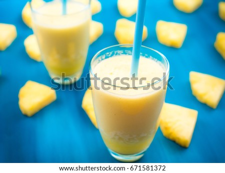 pineapple juice in a glass and pineapple fruits lying around #671581372
