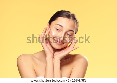 Young woman on a yellow background applies cosmetic face cream. #671584783