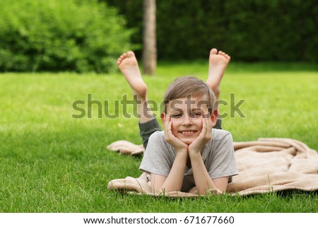 Cute young boy resting on the green grass - summer time, picnic #671677660