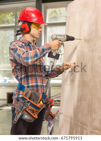 The builder performs repair of the premises. In a helmet, goggles with tools. #671795911