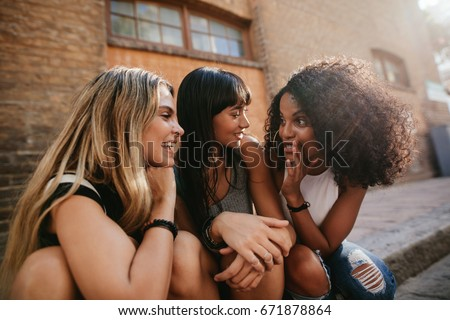 Shot of three beautiful girls sitting outdoors by the road and gossiping. Female friends relaxing by street and talking. #671878864