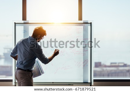 Businessman making a presentation at office. Entrepreneur using whiteboard to present ideas for business planning and decision making. Royalty-Free Stock Photo #671879521