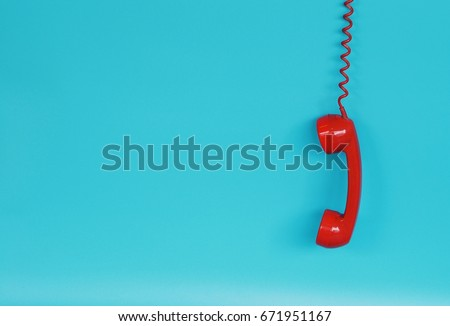 Red telephone receiver over blue background color with copy space Royalty-Free Stock Photo #671951167