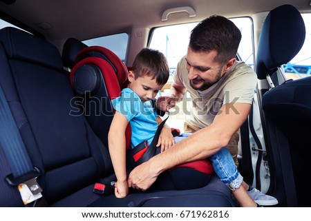 Close-up shot of concentrated father helping his son to fasten belt on car seat #671962816