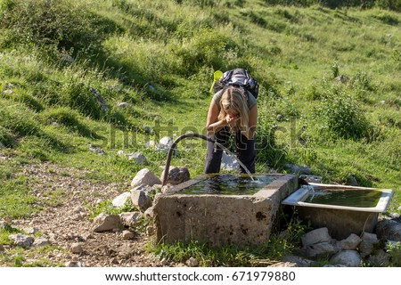Blonde adult women drink water on Mountain Fountain #671979880