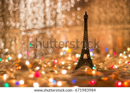 The Eiffel model is placed on a wooden table surrounded by light. Blurry background. #671983984