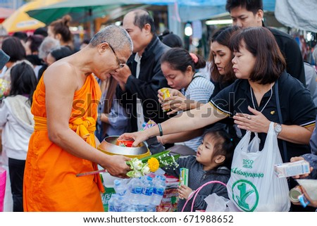 BANGKOK - APRIL 13 : The Buddhist Alms Giving Ceremony in Bangkok on April 13, 2017. Thai monks receive food from Buddhists on traditional Thai New Year Day. #671988652