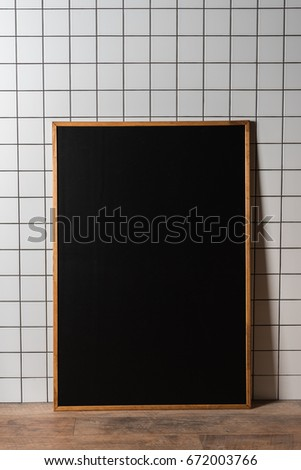 empty chalkboard in wooden frame standing at white tiled wall #672003766