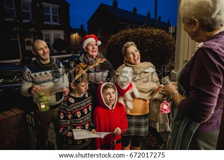 Three generation family are doing door-to-door carol singing. There is a senior woman at the door, appreciating their singing.