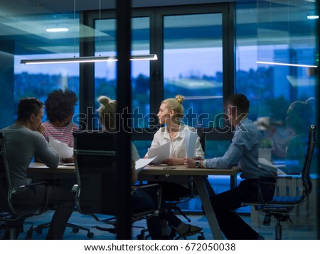 Multiethnic startup business team on meeting in modern night office interior brainstorming, working on laptop #672050038