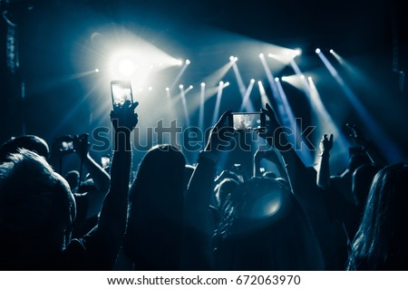 People in the crowd at a concert make video recordings and pics on a smartphone of published in social media