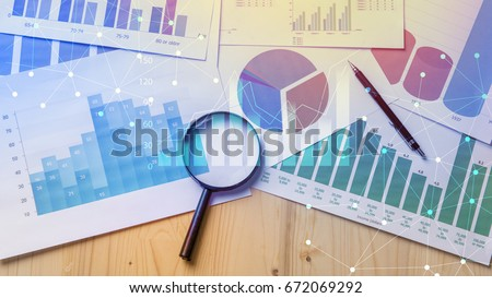 Magnifying glass and documents with analytics data lying on table,selective focus Royalty-Free Stock Photo #672069292
