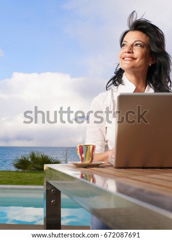 Woman on laptop out doors on decking #672087691