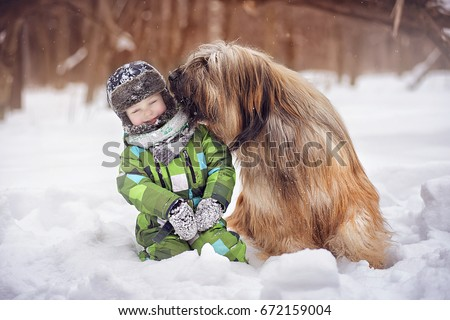 Dog breed Briard licked the little boy's cheek on a winter day #672159004