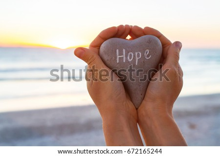 hope concept, hands holding stone with word written on it