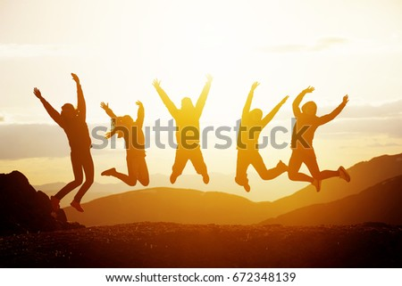 Group of five happy friends jumps at sunset time on background mountains #672348139