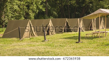 Green lawn with some green camping tents. #672365938