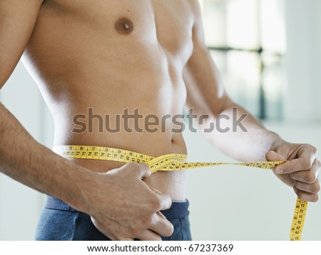 cropped view of caucasian young man measuring waist with yellow tape. Horizontal shape, mid section, side view #67237369