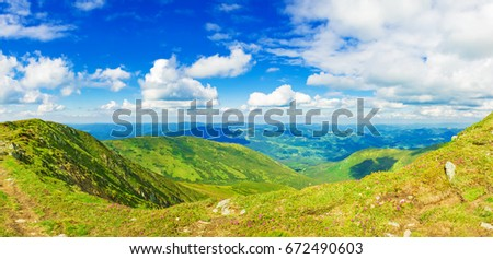Panoramic view of the sky and mountain ridges from the top of the mountain in a sunny summer day #672490603