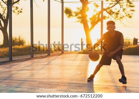 young black handsome man playing basketball on sunrise, morning sports, healthy lifestyle, having fun #672512200