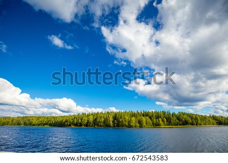 Lakeshore with trees and blue sky. Beautiful nature Finland.  #672543583