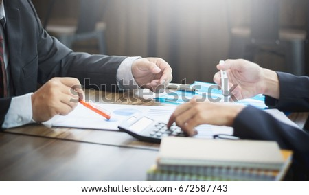 Two Asian businesspeople are analyzing a notebook pen, placed on a desk. #672587743
