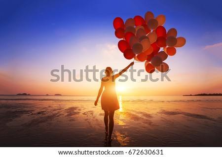 inspiration, joy and happiness concept, silhouette of woman with many flying balloons on the beach Royalty-Free Stock Photo #672630631