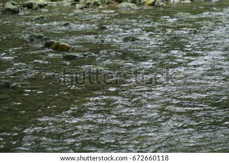 Tropical river with fast water current. River water photo texture. Green river in tropics wallpaper. Still rippled water of fresh spring in forest. Rippled river texture. Natural water current closeup #672660118