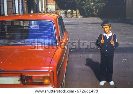 USSR, LENINGRAD - CIRCA 1982: Vintage photo of little first grader with backpack in his yard at red family soviet Lada car in Leningrad, USSR