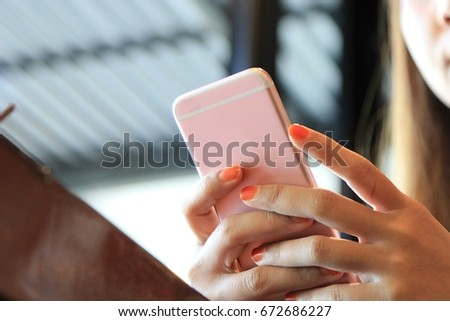 A young woman using smartphone on wooden table at the coffee shop. #672686227