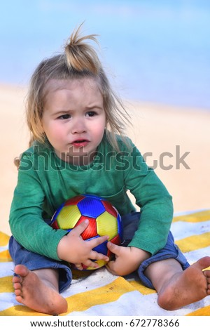 Boy with serious face sitting and playing with colorful ball at beach in sunny summer day on natural background outdoor #672778366