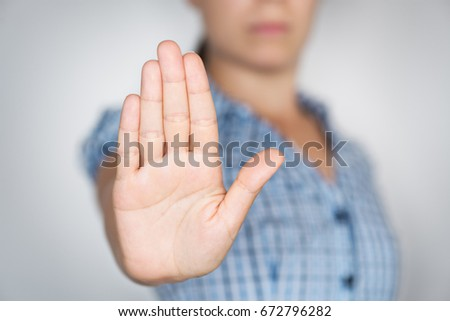 Young girl gesturing ALT or STOP with hand Royalty-Free Stock Photo #672796282
