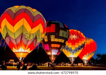 Four hot air balloons preparing to rise in the early morning dawn #672798970