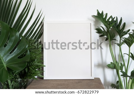 white photo frame with green leaf. environment  concept
