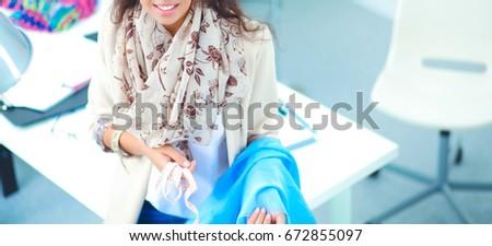 Smiling female fashion designer sitting at office desk #672855097