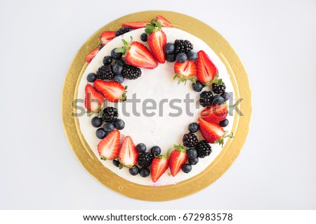 Cake with whipped blue and pink cream, fresh strawberries, blueberries and blackberry. Top view. Picture for a menu or a confectionery catalog.