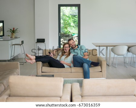 Young couple on the sofa watching television together in their luxury home #673016359