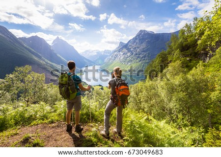 Two hikers at viewpoint in the mountains enjoying beautiful view of the valley with a lake and sunny warm weather in summer, green trees around #673049683