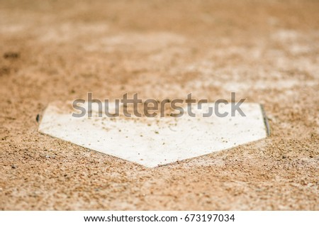 Home plate surrounded by dirt on a baseball field  #673197034