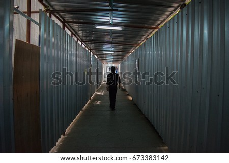 Silhouette man walking in a dark construction tunnel #673383142