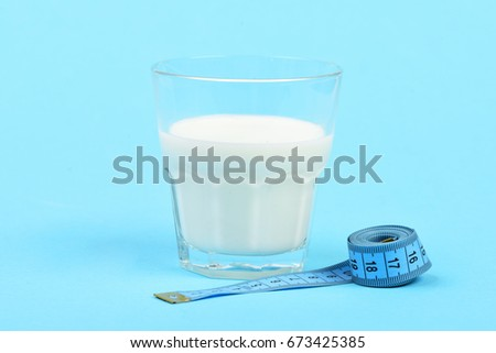 Roll of measuring tape next to glass of milk isolated on light blue background. Symbol of dietary nutrition #673425385