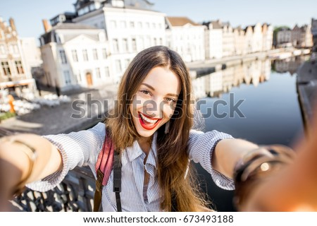 Young woman tourist making selfie photo standing on the bridge with beautiful view on Gent city in Belgium #673493188