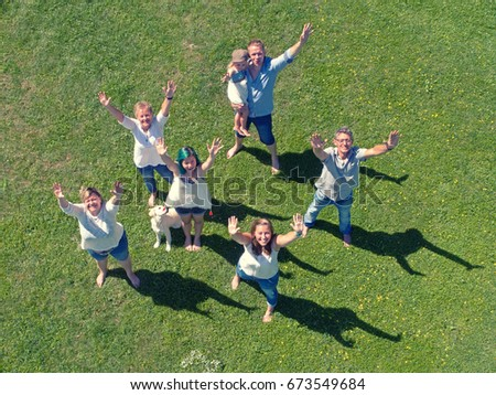 Family and summer holidays concept. Group of people having fun on the green meadow at beautiful sunny day. #673549684