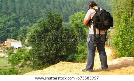 BANGKOK, THAILAND MAY 7, 2015 -  the photographer on a nature background, hipster man in a white shirt, with a camera #673585957