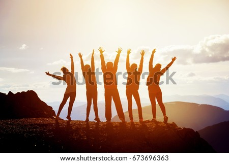 Five happy friends having fun standing with raised arms on mountain top at sunset time #673696363
