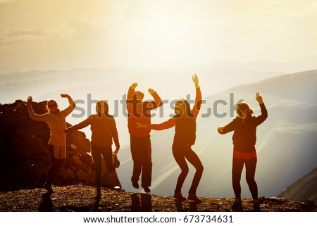 Five happy friends dancing on mountain top at sunset time #673734631