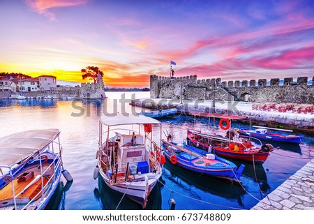 Old Greek port Nafpaktos with ancient castle walls an background and fishing boats at foreground. Epic lilac colored sunrise sky over sea scenery. Nafpaktos is famous  travel destination in Greece.