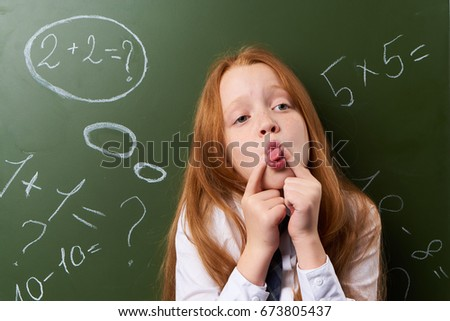 Schoolgirl on a blackboard background                                #673805437