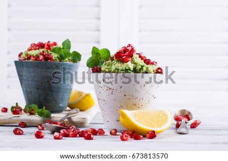 Green couscous with pomegranate and mint on a wooden background. Selective focus. #673813570